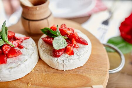 Grilled camembert cheese with strawberry, honey and basil leaves, delicatessen, camembert cheese fondue on the dinner table.