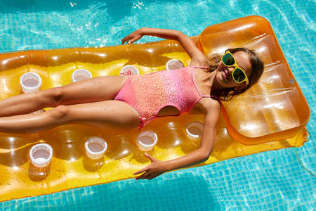 Little girl in sunglasses relaxing in swimming pool, enjoying suntans, swims on inflatable yellow mattress and has fun in water on family vacation, tropical holiday resort, view from above, copy space.