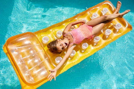 Happy little girl has fun in swimming pool, swims on inflatable yellow mattress on family vacation, tropical holiday resort, view from above, copy space.