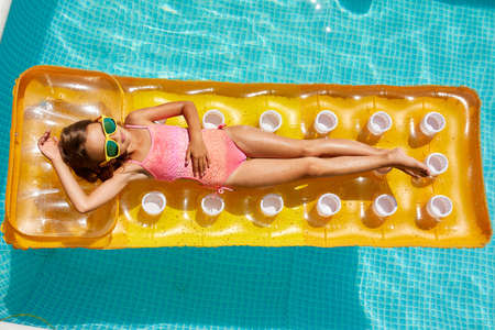 Little girl in sunglasses relaxing in swimming pool, enjoying suntans, swims on inflatable yellow mattress and has fun in water on family vacation, tropical holiday resort, view from above, copy space. Stockfoto