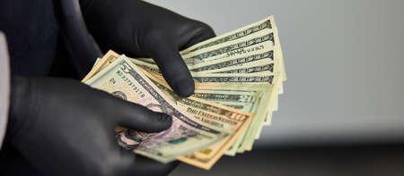 Man holding money dollars in hand in black medical gloves. Save money.