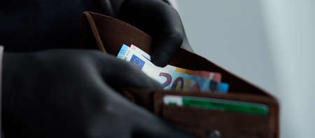 Man holding a wallet with money euro in hand in black medical gloves. Save money. The world crisis Foto de archivo