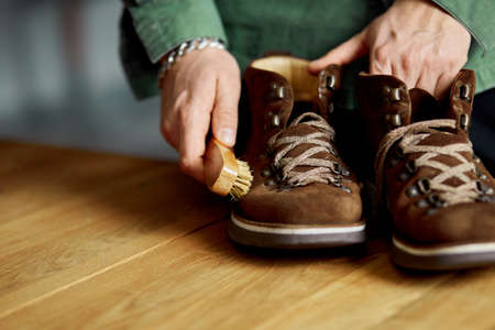 Man's hand clean suede shoes, boots with a brush on wooden background. Footwear maintenance captured, copy space, for text.
