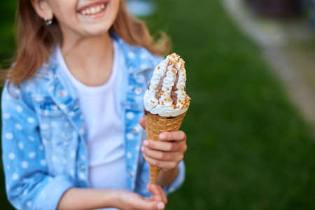 Cute girl with italian ice cream cone smiling and looking at camera while resting in park on summer day, child enjoying ice cream outdoor, happy holidays, summertime