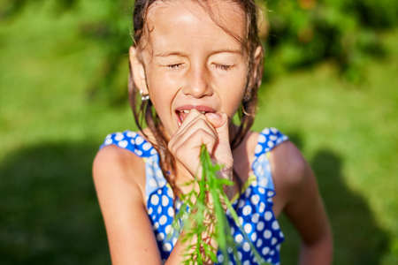 A young girl holds and eat a carrot that she picked from her family's garden, organic homemade vegetables harvest