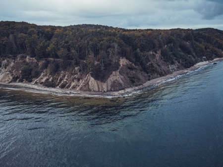 Cliff on sea shore at sunrise. Baltic sea in autumn from drone.Nature from a birds eye view. From air.