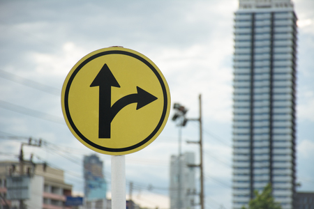 pointed arrows: Sign turn right or go straight with skyscraper Stock Photo