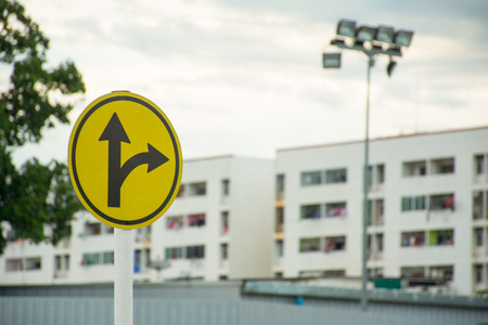pointed arrows: Sign turn right or go straight with blur city background
