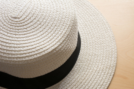 white wood floor: Beautiful white beach hat on wood floor