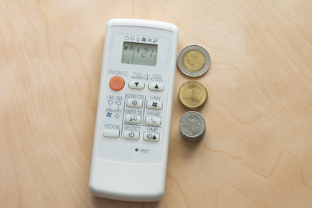 wasteful: Wasteful spending air condition remote with coin, Top view