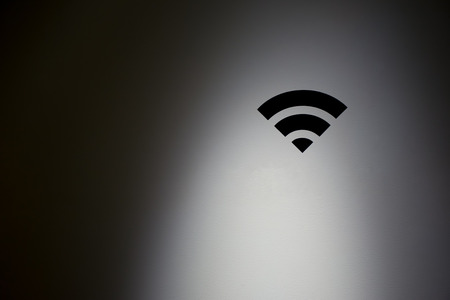 payphone: WiFi symbol in highlight concrete wall.