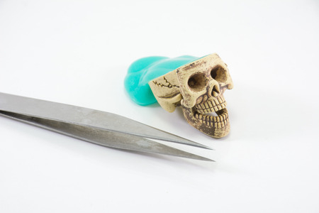 tongs: Cerebrum in a skull head and medical tongs on white background
