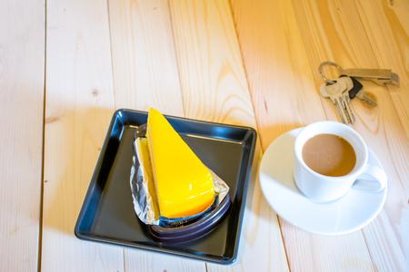 orange cake: Coffee cup with orange cake in the morning sunshine on wood floor.