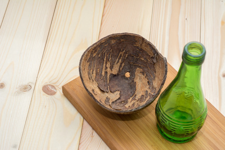 splat: Coconut shell with green glass bottles on splat, coconut oil. Stock Photo