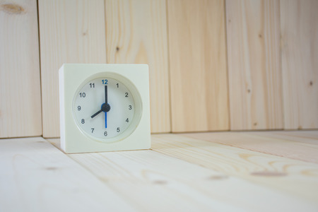 oclock: The time is now 8.00 am, on wooden table. Stock Photo