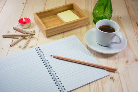 dim light: Blank Note and pencil with wooden table in dim light, coffee.