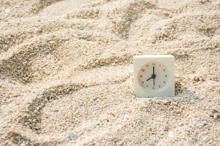 hight: Clock on sand with hight sunlight.