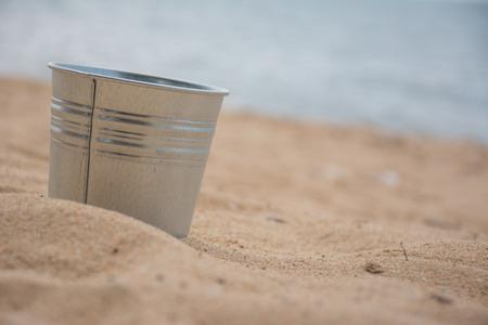 aluminium: Little aluminium tank on the beach with sea in background