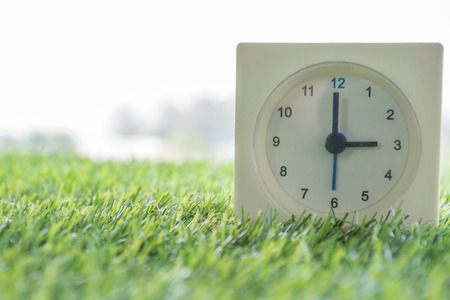 Time is Three o'clock in the evening, clock on artificial green grass. Imagens - 47239580