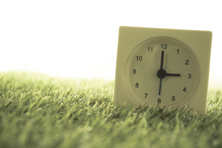 Time is Three oclock in the evening, clock on artificial green grass. - Vintage dream filter