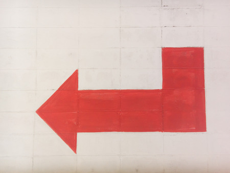 turn left sign: Red arrow turn left sign on concrete wall