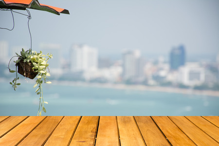 ivy hanging: Wooden table with Hanging decorate green ivy plants and sea blurred  in background, summer concept - can be used for display or montage your products