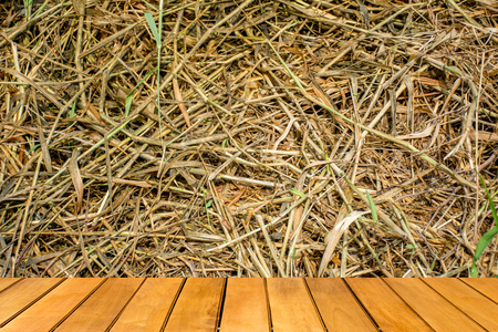 disconsolate: Wooden table with Dead grass, use for background or texture Stock Photo