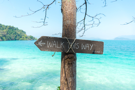 Walk this way sign on the beach with sea at koh wai, trat, thailand - coast path public footpath signs.