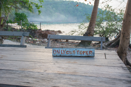 Only customer sigh on wooden table with beautiful sea on background.