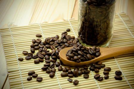 Coffee bean in wooden spoon.