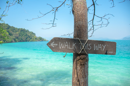 footpath: Walk this way sign on the beach with sea at koh wai, trat, thailand - coast path public footpath signs.