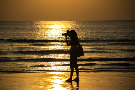 Female photographer at sunset on the beach, chao lao beach chanthaburi , Silhouette style. Imagens