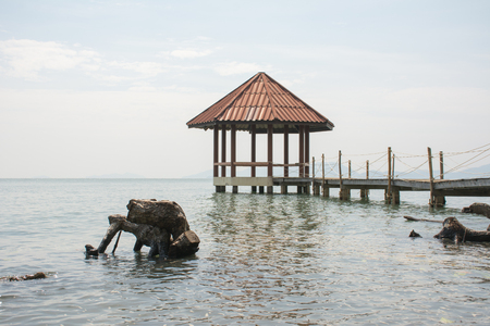 Summer, Travel, Vacation and Holiday concept - Beautiful wooden pier at a beach in Black sand beach, Trat, Thailand.