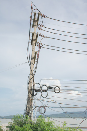 Electricity post with messy wire and tilted in thailand, selective focus.