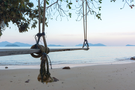 Swings at tree on the sand beautiful tropical beach in the evening at koh wai island, Trat, Thailand.