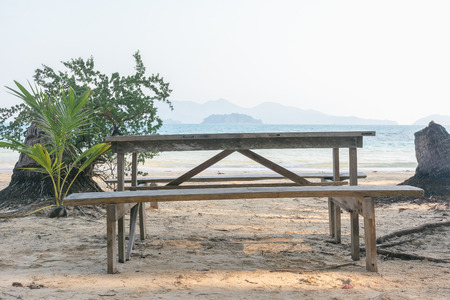 Wooden table and chair on sand at koh wai island, trat, thailand. Imagens