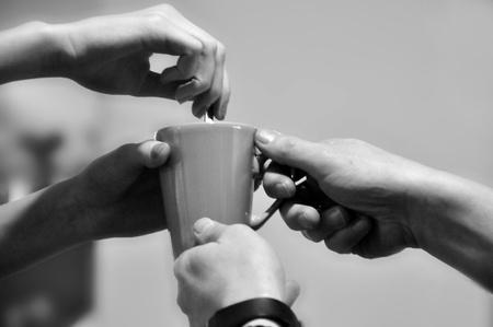 drank: vier handen die samen een kopje vasthouden