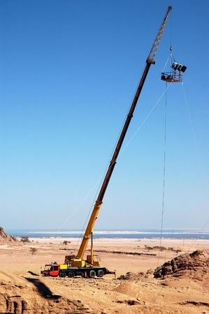 lifting/hoisting crane loaded with floodlight for film shooting. Stock Photo
