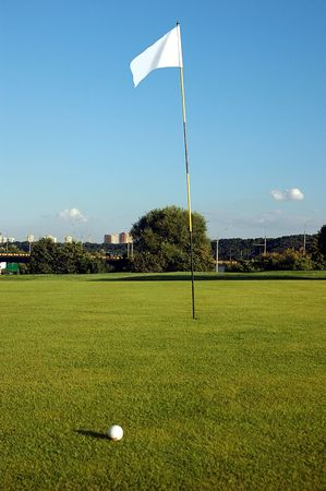 Golf field with ball and flaf