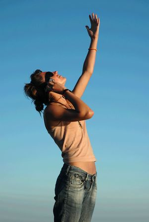 Young woman speaking on mobile phone looking up to the sky