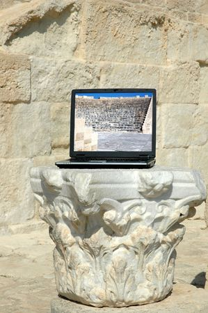 Laptop with picture of greek amphitheatre standing on the flat marble stone. Cyprus. Stock Photo