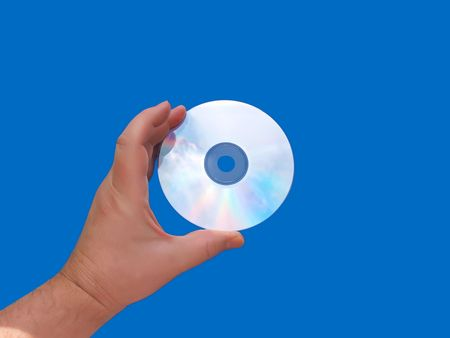 A hand holding a sun lit CD or DVD media reflecting the sky against a blue background