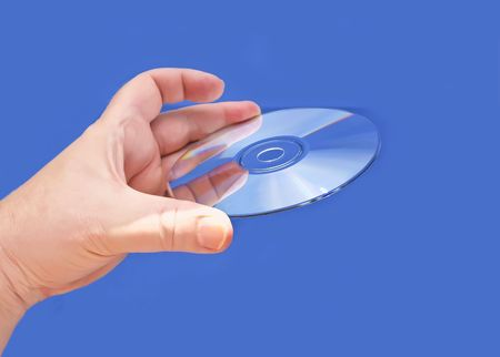 A hand holding a CD or DVD media against a blue background Stock Photo