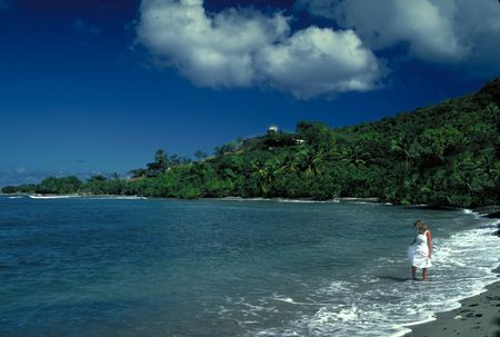 A pretty woman girl in a white dress in the warm water surf at St. Croix Island in US Virgin Islands. Stock Photo