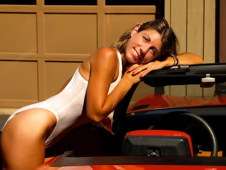 leans: Pretty girl in swimsuit leans on a sports car