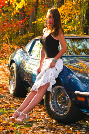 Pretty girl in dress leaning on car in fall leaves and foliage Stock Photo