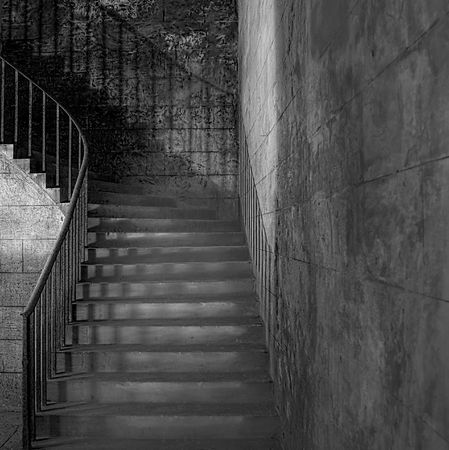 Monochrome shot of sandstone shadowy staircase with rusted handrail (circa 1854)