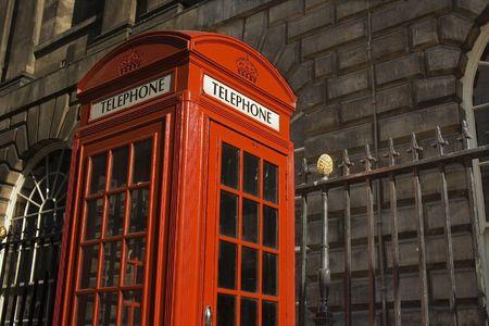 Classic bright red British telephone box set against ornate building Stock Photo