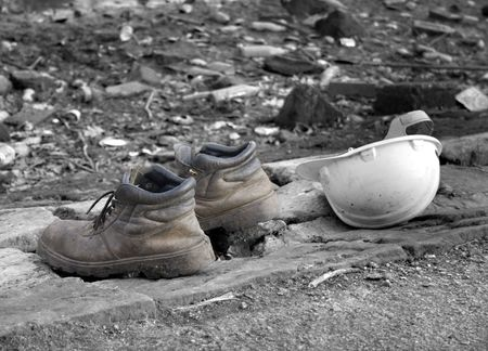 footware: Pair of old work boots with builders hard hat,(selective color) Stock Photo