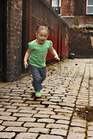 Young black  girl playing on cobble stoned alley photo